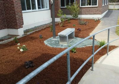 Coos County Nursing Home Berlin NH landscaping after bench and flowers