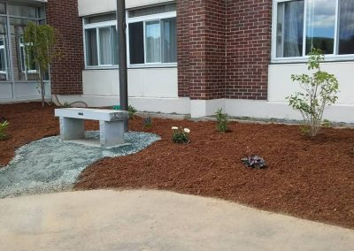 Coos County Nursing Home Berlin NH landscaping after with bench, flowers, mulch, trees